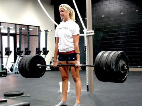 Young woman deadlifts a heavy weight. Muscle building is vital for health and strength, whoever you are