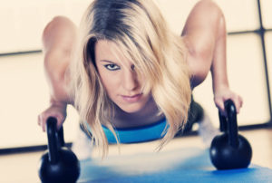 Woman doing push ups with kettlebells