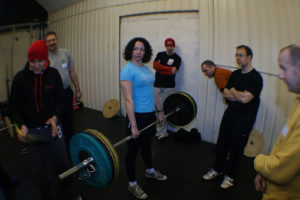 Woman deadlifting watched by a group of guys