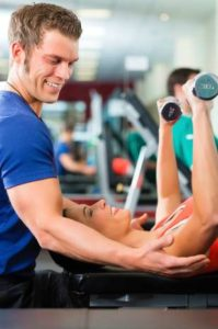Man grinning while spotting woman doing chest press