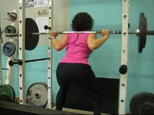 Woman squatting in power cage