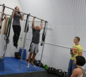 Woman doing pull ups next to man