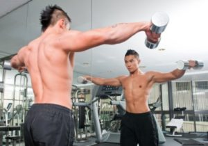 Shirtless guy lifting weights looking at himself in mirror