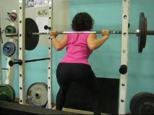 Woman squatting in squat rack