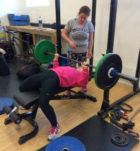 Julia showing how to go to failure on the bench press with a good spotter