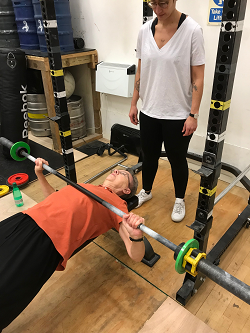 Pat doing bench press in a strength ambassadors ladies who lift class